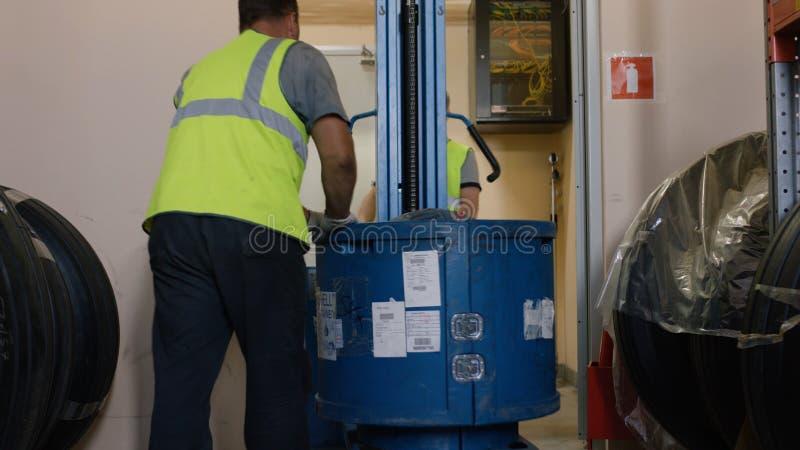 De arbeiders laden goederen op een vrachtwagen en genomen aan het pakhuis De arbeidersbestuurder van het werknemerspakhuis in een royalty-vrije stock fotografie