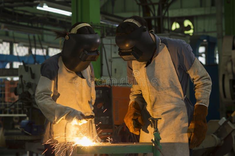 De arbeiders lassen metaal stock afbeelding