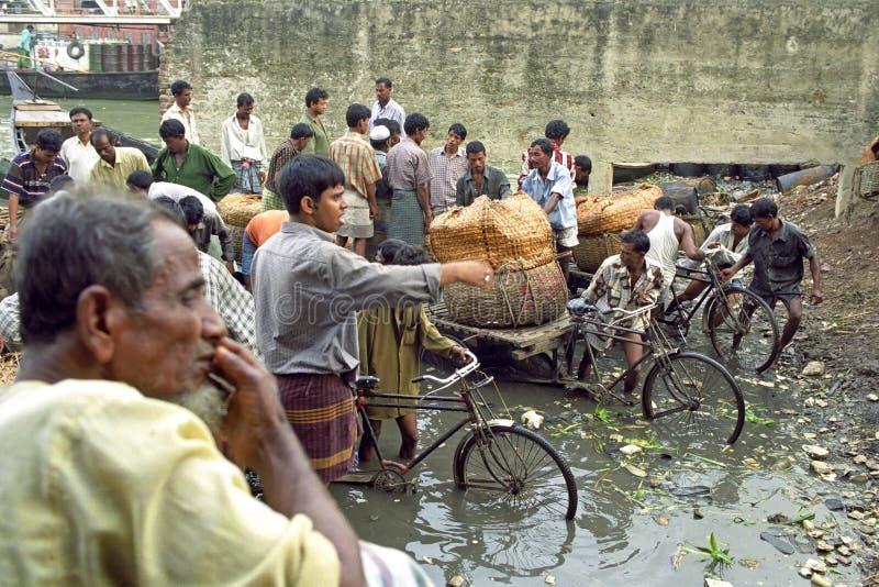 De arbeiders maken boten in bezige haven Dhaka leeg royalty-vrije stock afbeeldingen