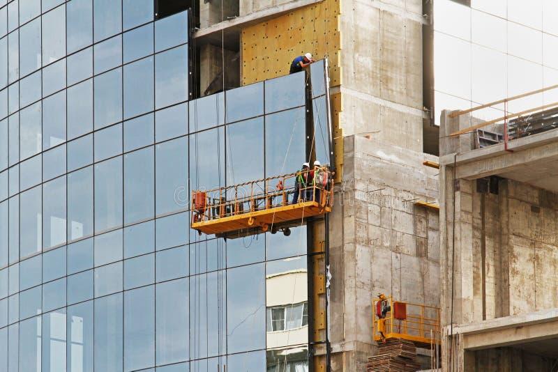 De arbeiders op de steigerlift installeren glasvenster op voorgevel van de nieuwe bouw in Volgograd royalty-vrije stock foto's