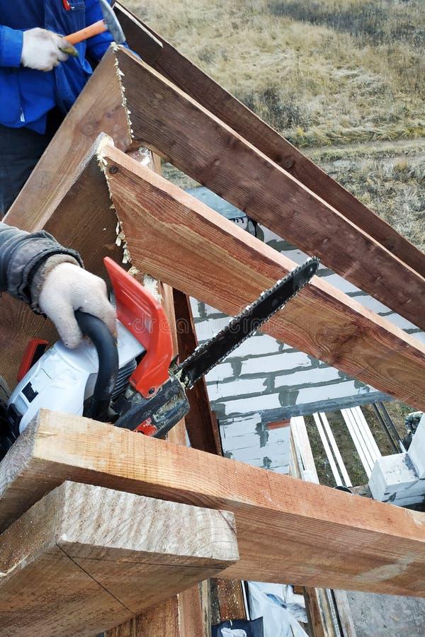De arbeiders snijden de daksparren op het dak van het kettingzaaghuis royalty-vrije stock foto