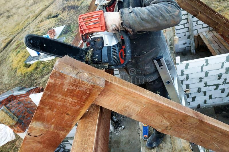 De arbeiders snijden de daksparren op het dak van het kettingzaaghuis stock fotografie