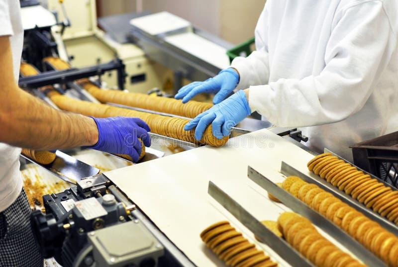 De arbeiders sorteren koekjes op een transportband in een fabriek - producti royalty-vrije stock afbeelding