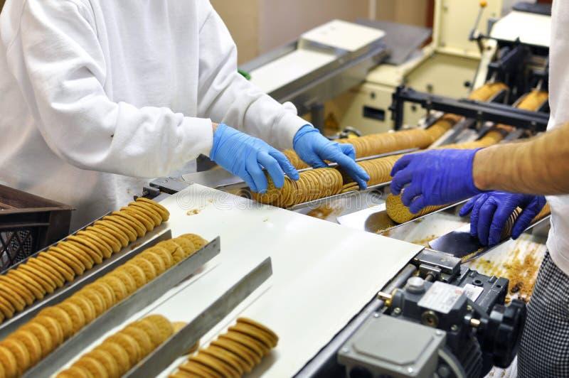 De arbeiders sorteren koekjes op een transportband in een fabriek - producti royalty-vrije stock afbeeldingen