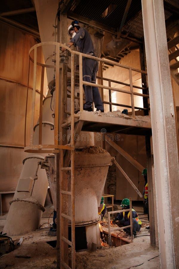 De arbeiders van de cementfabriek stock foto's