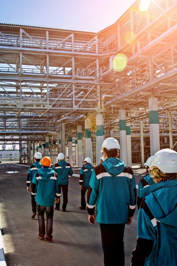 De arbeiders van chemische fabriek in werkkledij loopt dichtbij grote pijpleidingsbouw aan hun werkplaatsen royalty-vrije stock afbeeldingen