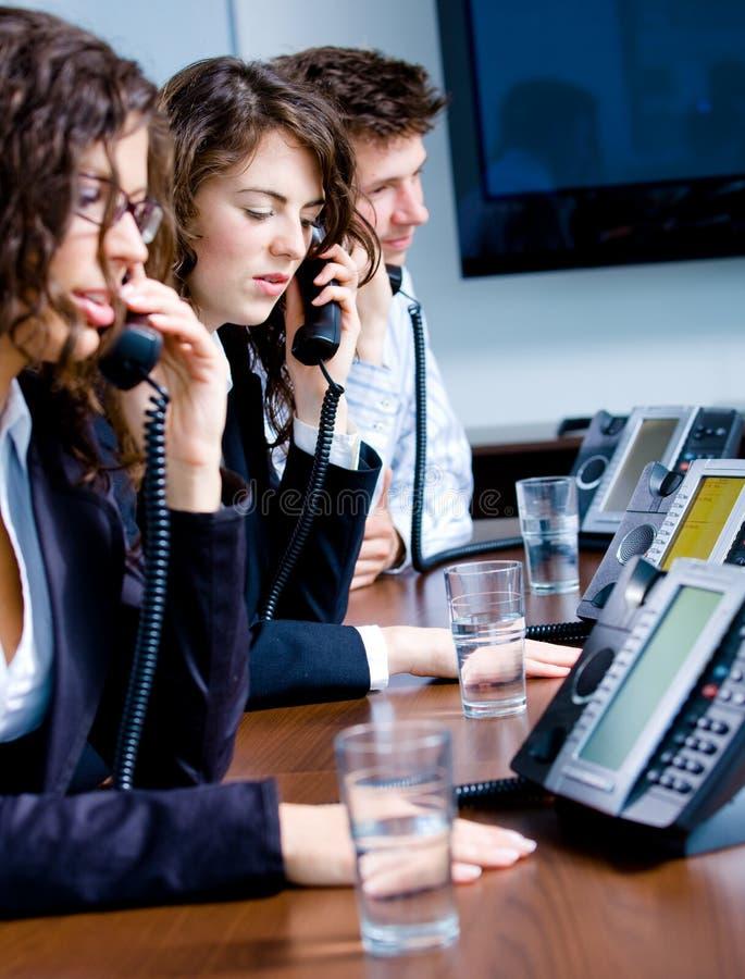 De arbeiders van de telefoon op kantoor stock foto's
