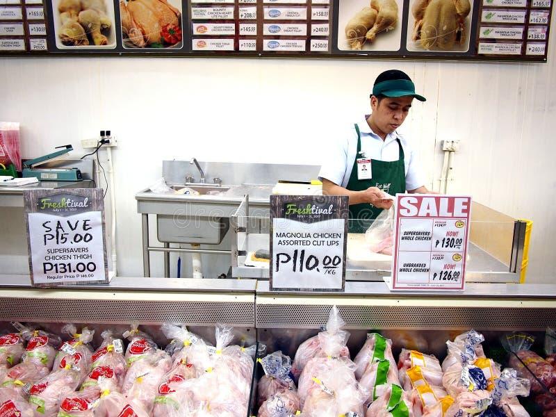 De arbeiders van een kruidenierswinkelopslag hakt op vers vlees bij een vleessectie van een kruidenierswinkel voor een klant stock afbeelding