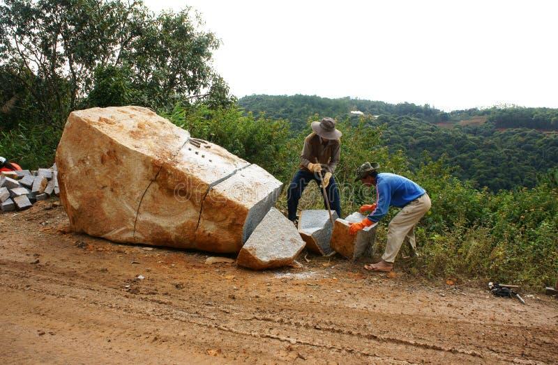 De arbeiders verdelen grote rots voor wegwerkzaamheden stock foto's