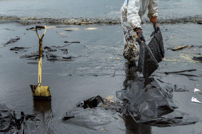 De arbeiders verwijderen en maken ruwe olie schoon met absorberende pap wordt gemorst die stock foto's