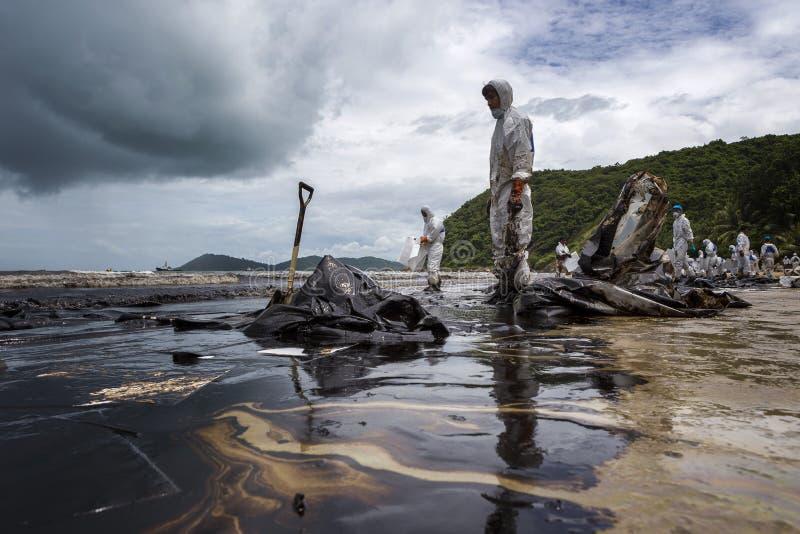 De arbeiders verwijderen ruwe olie uit een strand royalty-vrije stock afbeeldingen