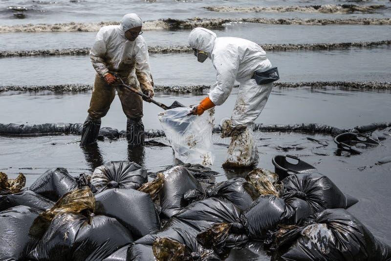 De arbeiders verwijderen ruwe olie uit een strand stock foto