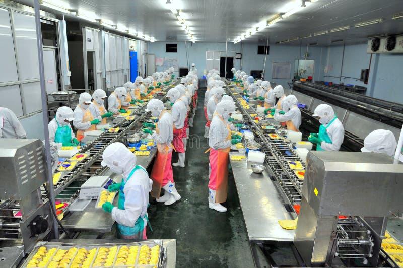 De arbeiders werken hard aan een productielijn in een zeevruchtenfabriek in Ho Chi Minh-stad, Vietnam royalty-vrije stock foto's