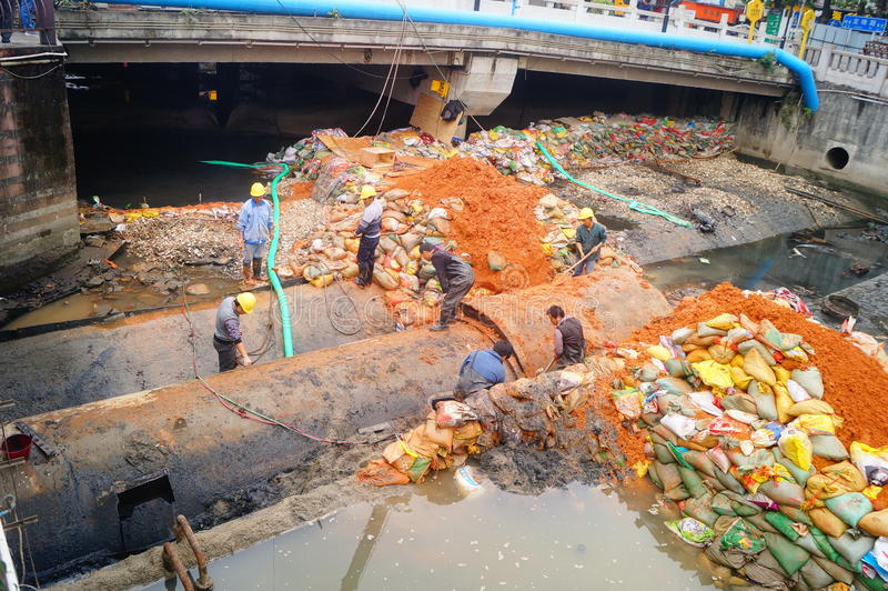 De arbeiders zijn op het de pijpleidingsonderhoud van de rivierdrainage royalty-vrije stock afbeeldingen