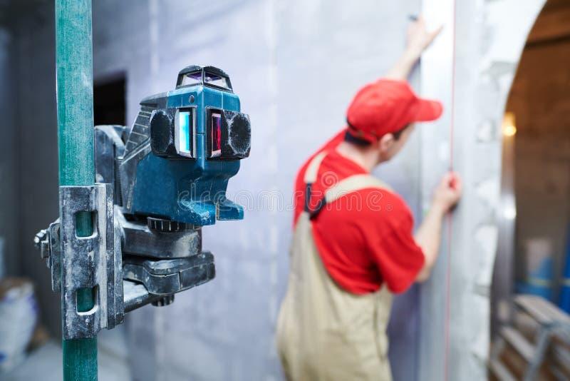 De arbeidersmaatregel en teken van de huisvernieuwing door lijnlaser royalty-vrije stock afbeeldingen