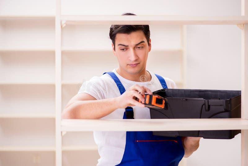 De arbeidersman die het assembleren boekenrek herstellen stock afbeeldingen