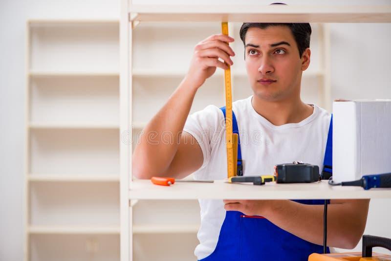 De arbeidersman die het assembleren boekenrek herstellen stock fotografie