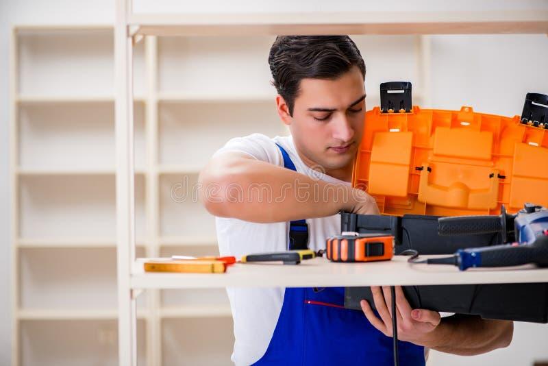 De arbeidersman die het assembleren boekenrek herstellen royalty-vrije stock foto