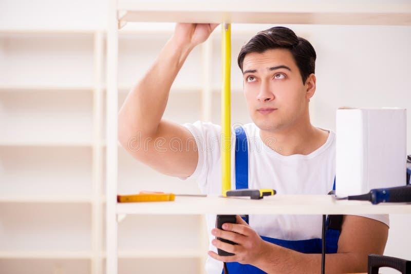 De arbeidersman die het assembleren boekenrek herstellen stock foto