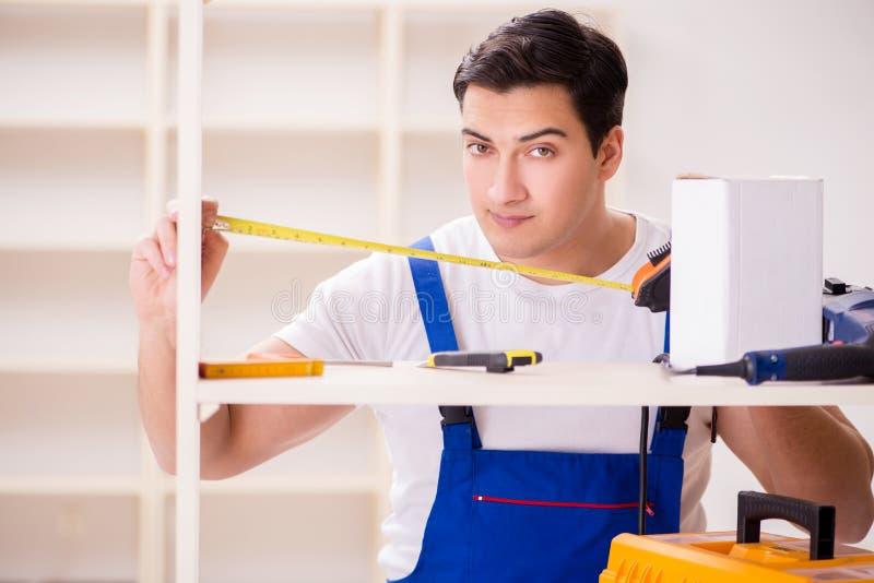 De arbeidersman die het assembleren boekenrek herstellen stock afbeelding