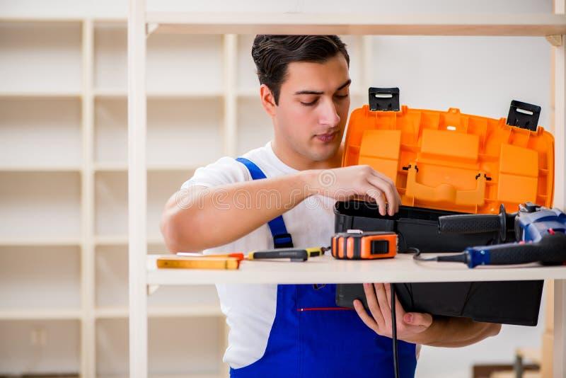 De arbeidersman die het assembleren boekenrek herstellen stock foto's