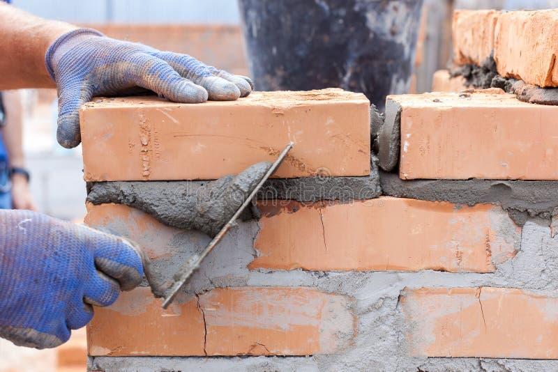 De arbeidersmetselaar die van de bouwmetselaar rode baksteen met het mes van de troffelstopverf in openlucht installeren stock fotografie