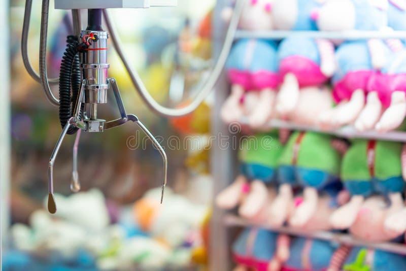 De arcade van de klauwkraan met stuk speelgoed beloningen op de achtergrond: sluit omhoog van de Robotachtige Klauw van Chrome Op royalty-vrije stock fotografie