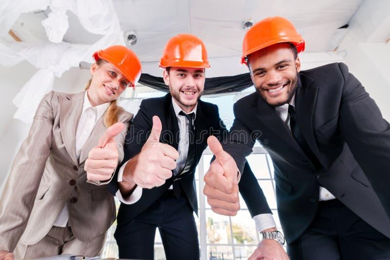 De architecten tonen duimen Drie ontmoete businessmеnarchitect royalty-vrije stock foto's