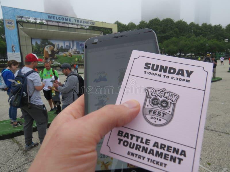 De arena van de trainerslag in Pokemon gaat Fest met een hand houdend een telefoon en van de toernooieningang kaartje royalty-vrije stock foto