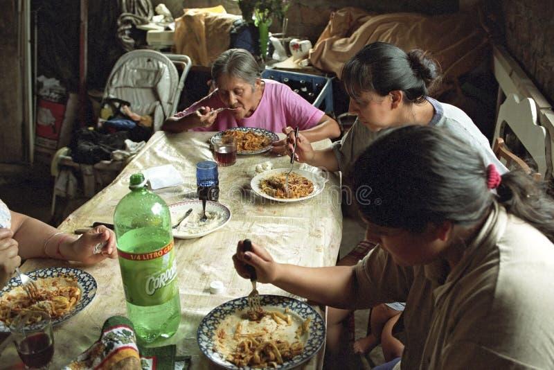 De Argentijnse familie met slechts vrouwen eet in krottenwijk stock fotografie