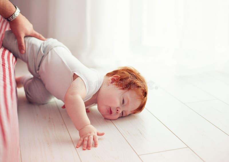 De armen weinig peuterbaby vielen onderaan van het bed terwijl het kruipen op het Papa wordt gemist die om hem te vangen stock fotografie