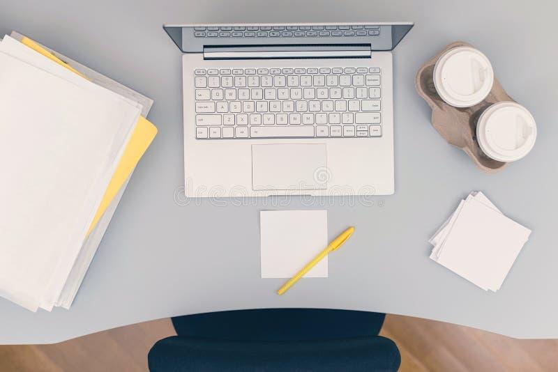 De arriba hacia abajo de pieza del sitio de la oficina incluyendo una tabla, una silla, un ordenador portátil, tazas de café de p fotos de archivo