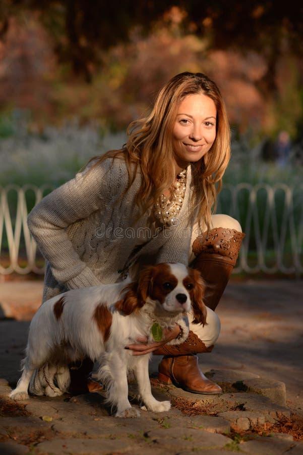 De arrogante hond van Koningscharles spaniel en een meisje zijn samen in het park genietend van mooie de herfstdag stock fotografie