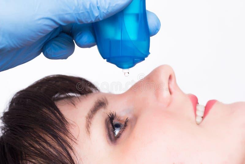 De arts begraaft bevochtigende en vasoconstrictor oogdalingen aan een Kaukasisch meisje, close-up, exemplaarruimte stock foto