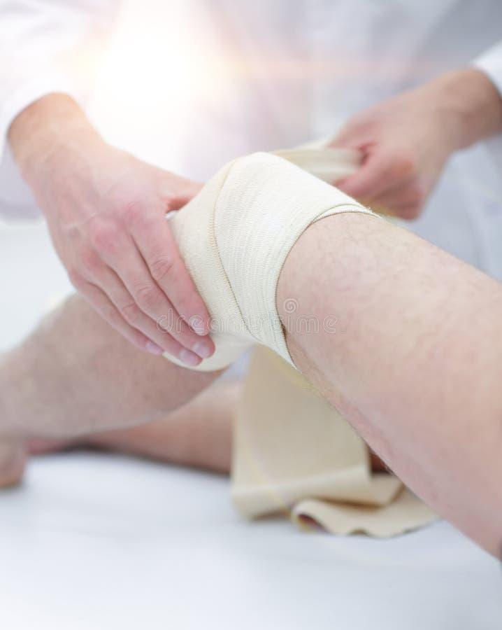 De arts behandelt wond op het geduldige been van ` s in een kliniekruimte royalty-vrije stock fotografie
