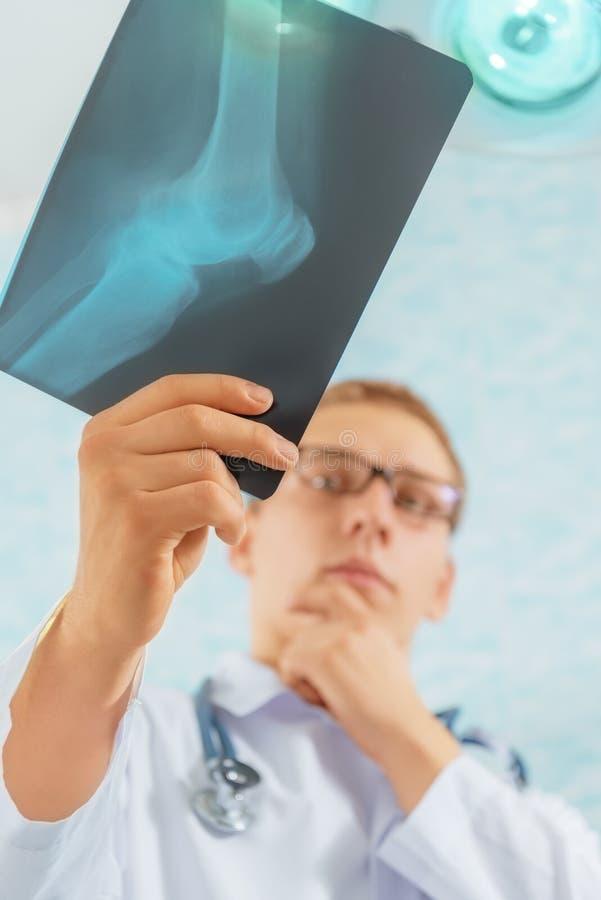 De arts bekijkt x-ray beeld van knieverbinding royalty-vrije stock afbeelding