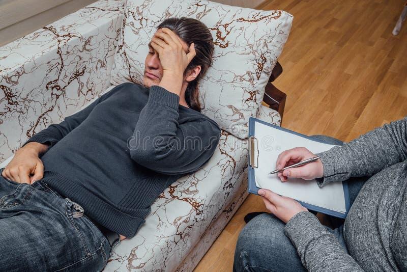 De arts bezoekt zijn patiënt Zieke droevige mens die met arts over zijn problemen spreken De arts schrijft nota's stock fotografie