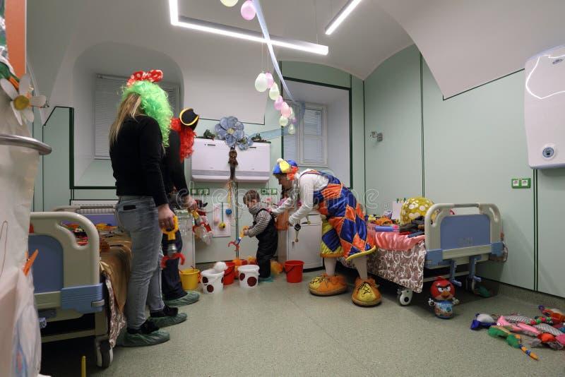 De arts in clownkostuum onderzoekt het kind stock foto's