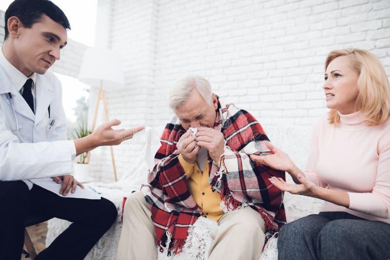 De arts communiceert met de oude mensen` s vrouw, die naast hem zit en zijn neus blaast stock foto