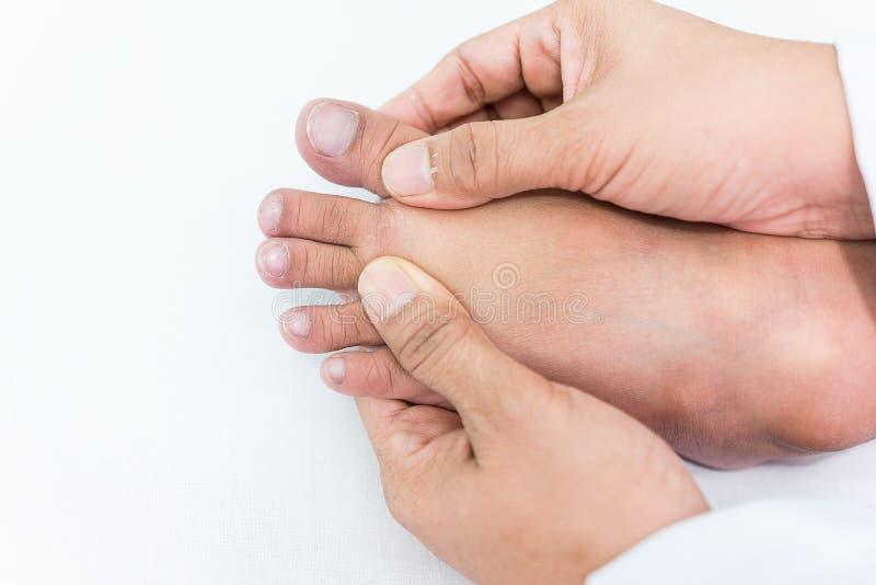 De arts controleert een geduldige teenspijkers van ` s dat kind omdat de kind` s ongebruikelijke spijkers de symptomen van de zie royalty-vrije stock afbeelding