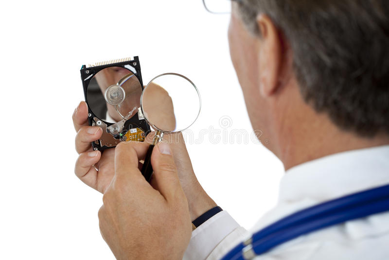 De arts controleert harde schijf met vergrootglas stock afbeelding