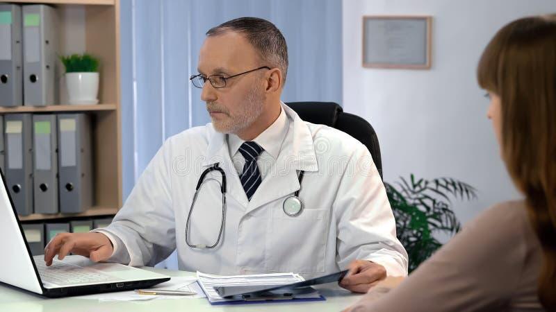 De arts die analyse controleren op laptop, die x-ray, digitale apparaten houden vervangt document royalty-vrije stock afbeelding