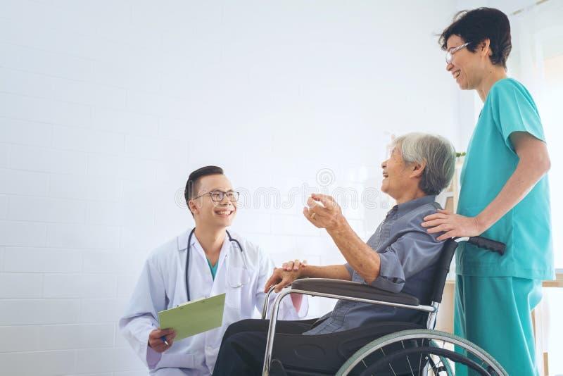 De arts die bejaarde geduldige ` s houden dient een wheelchai in, gevend su royalty-vrije stock fotografie