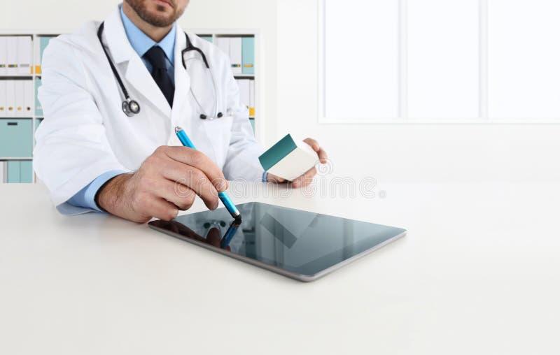 De arts die tablet op bureaubureau gebruiken schrijft de geneeskunde voor royalty-vrije stock afbeelding