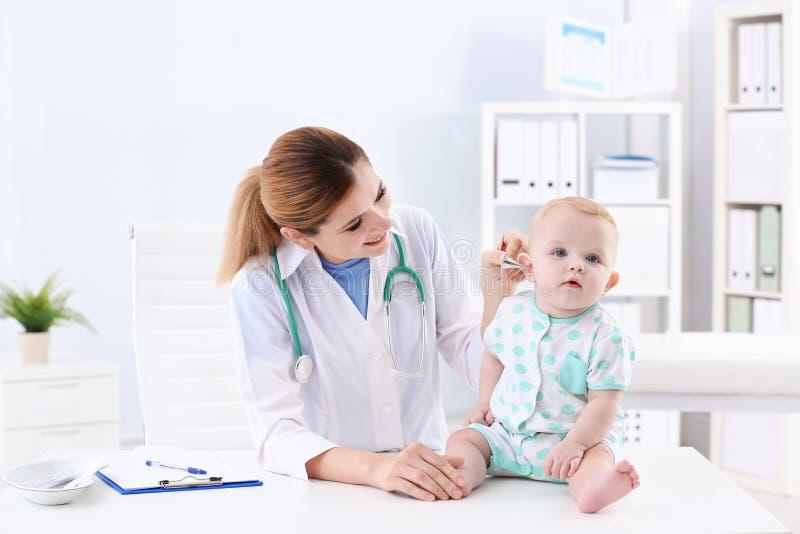 De arts die van kinderen het oor van de baby onderzoeken royalty-vrije stock foto's