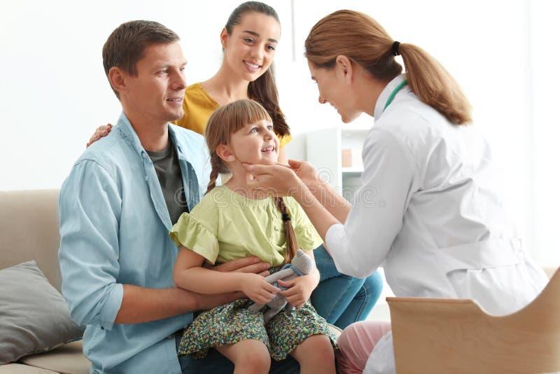 De arts die van kinderen meisje thuis onderzoeken dichtbij ouders stock afbeeldingen