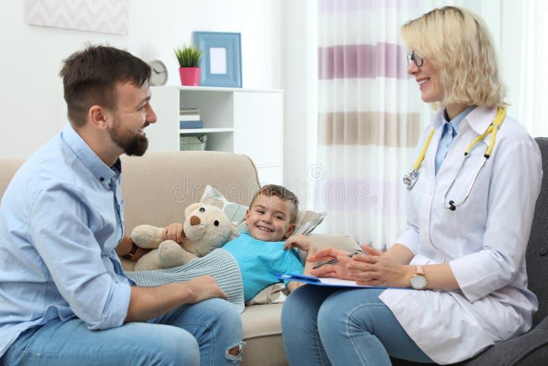 De arts die van kinderen weinig jongen bezoeken stock afbeeldingen