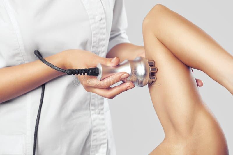 De arts doet de Rf-het opheffen procedure aangaande het hogere wapen van een vrouw in een schoonheidssalon stock foto