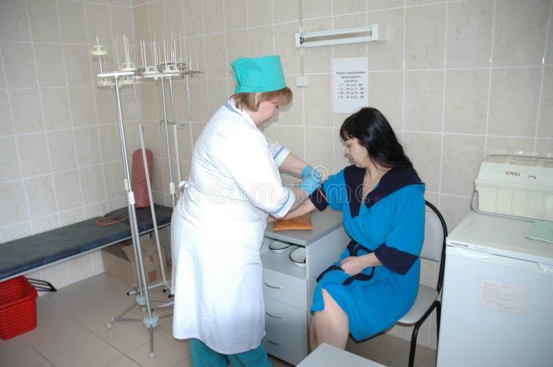 De arts in een medische kliniek neemt een bloedonderzoek royalty-vrije stock foto