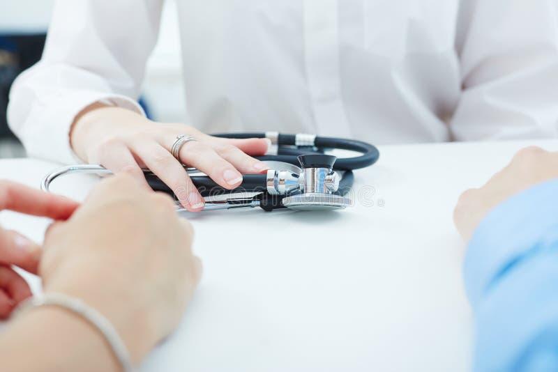 De arts en de patiënten bespreken iets, enkel handen bij de lijst royalty-vrije stock fotografie